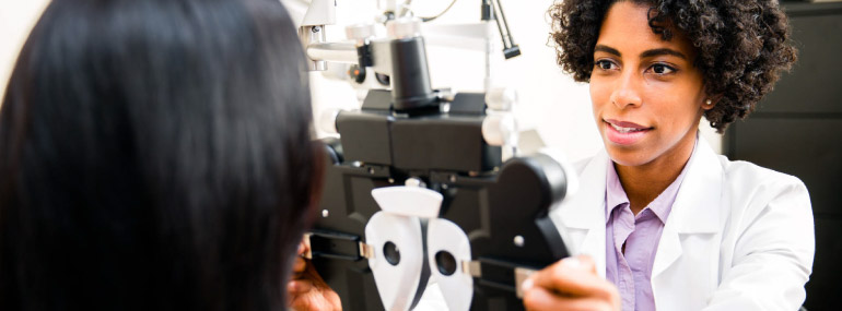Optometrist giving an eye exam to a woman.