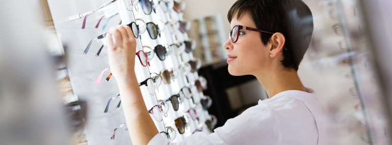 Woman looking through walls of eye glasses, searching for a new pair.